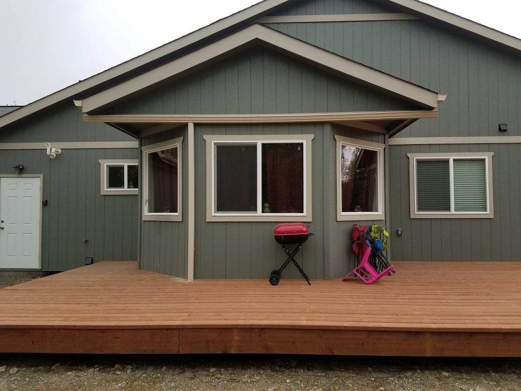 Olive green house with large wood deck