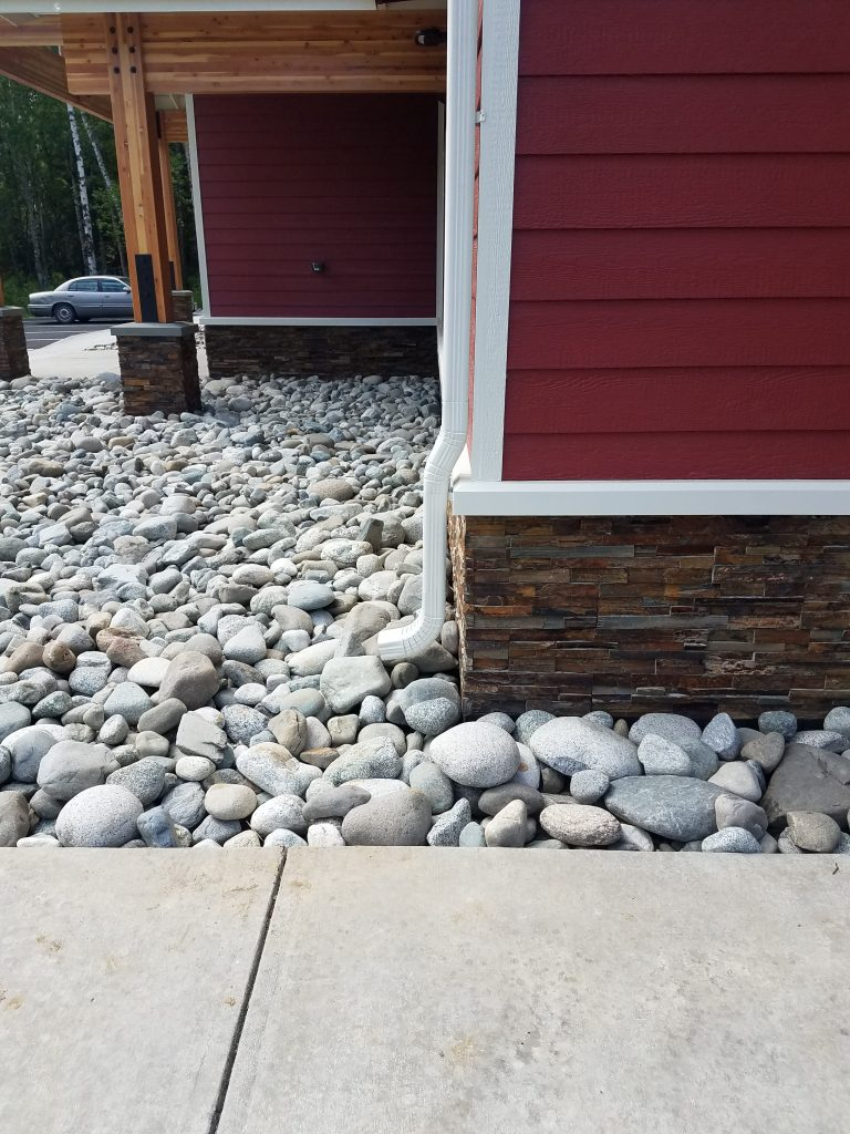 stone bed next to red house