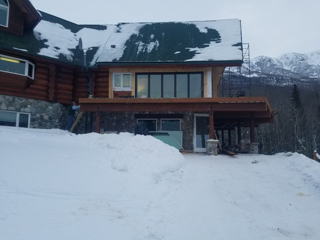 Lodge with deck overhanging snowing land